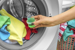 Hand pours liquid powder into the washing machine. Royalty Free Stock Images