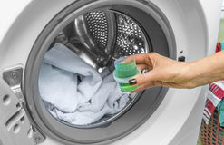 Hand pours liquid powder into the washing machine. Stock Photography