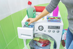 Hand pours liquid powder into the washing machine. Stock Images