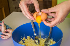 Hand pours out raw egg of the shell Royalty Free Stock Photos