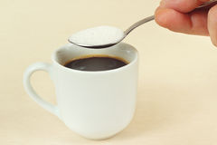 Hand pours sugar from spoon in a coffee cup Royalty Free Stock Photography