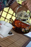 The hand pours teapot in cup tea Stock Photos