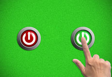 Hand and power button. Hand push  green button  on grass background Stock Photos