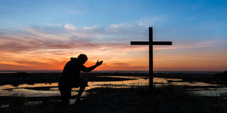 Hand of Prayer Sunset. An with the sunset behind him kneeling by a cross Royalty Free Stock Photography