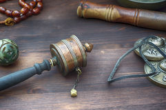 Hand prayer wheel. Among religious items on a wooden table Stock Image