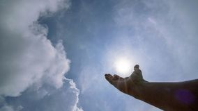 Hand praying for blessing from god on sun and clouds background,Christian Religion concept.  stock image