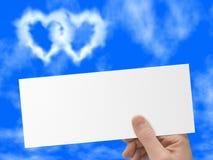 In hand prentbriefkaar, blauwe hemel en hart-vormige wolken Stock Afbeeldingen