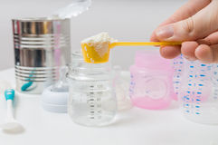 Hand is prepairing milk formula for feeding baby.  Stock Photo