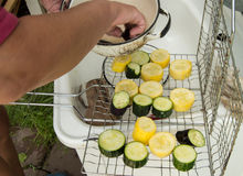 Hand prepares raw sliced vegetables - zucchini, squash, eggplant roasting on the grill.  Royalty Free Stock Images