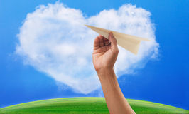 Hand preparing to throwing paper plane to mid air againt green g Stock Photo