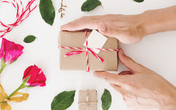Hand preparing Valentines gift, on white table, with roses and decoration Royalty Free Stock Photo