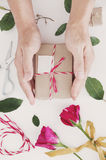 Hand preparing Valentines gift, on white table, with roses and decoration Stock Image