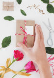 Hand preparing Valentines gift, on white table, with roses and decoration Stock Photography