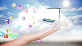 Hand presenting laptop and app icons in cloud Stock Photos