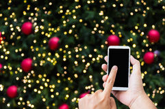 Hand press on big smartphone screen on Xmas New Year theme golde Royalty Free Stock Photos