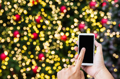 Hand press on big smartphone screen on Xmas New Year theme golde Stock Photo