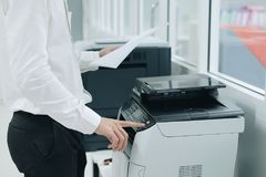 Hand press button on panel of printer scanner or laser copy machine in office stock photo