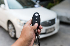 A hand press button of remote control car key to open a car door Royalty Free Stock Images