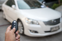 A hand press button of remote control car key to opens a car doo Royalty Free Stock Images