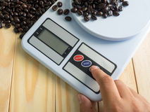 Hand press on  digital measuring device and coffee beans Stock Image