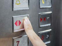 Hand press open door button in elevator Stock Photo
