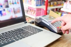Hand press with swiping credit card on ternimal and using laptop. Paying shopping online Royalty Free Stock Photo