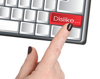 The hand presses the button DISLIKE. Female hand presses the red button DISLIKE, painted keyboard Stock Photos