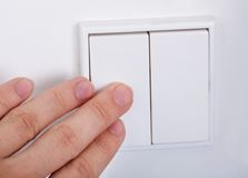 Hand presses the light switch on the wall Stock Photography