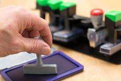 Hand presses stamp in stamp pad - Closeup stock images