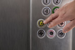 Hand pressing the alarm button in the elevator. Man pressing the alarm button in the elevator with his finger royalty free stock images