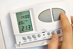 Hand pressing button on digital thermostat Royalty Free Stock Photo