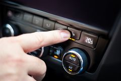 Hand pressing the button for heated seats in the car Royalty Free Stock Photo