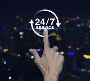 Hand pressing button 24 hours service icon over blurred light ci. Ty tower background, Full time service concept Stock Photography