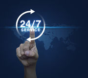 Hand pressing button 24 hours service icon over digital world map Royalty Free Stock Photos