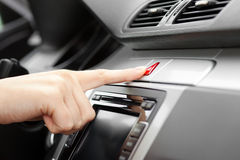 Hand pressing Car emergency lights button. On dashboard Royalty Free Stock Image