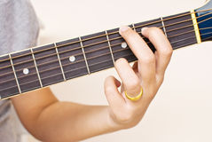 Hand pressing classic acoustic guitar chord. Stock Photos