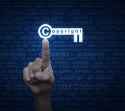 Hand pressing copyright key icon over computer binary code blue Stock Image