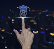 Hand pressing e-learning icon over blur light city tower backgro Stock Photo