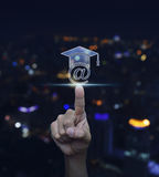 Hand pressing e-learning icon over blurred light city tower back Stock Images