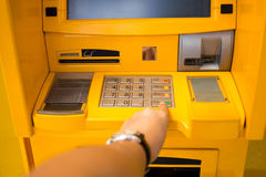 Hand pressing enter button on ATM bank machine Stock Photo