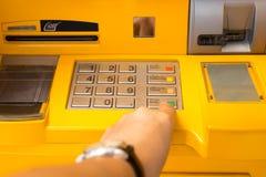 Hand pressing enter button on ATM bank machine. Hand pressing button on ATM bank machine Royalty Free Stock Photos