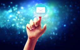 Hand pressing a envelope icon. Over technology blue background Stock Image