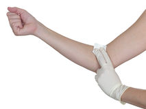 Hand pressing gauze on arm after administering an injection. Royalty Free Stock Photo