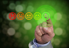 Hand pressing green smiley button of performance rating Royalty Free Stock Images