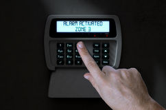 Hand Pressing Home Security System. A male hand pressing a button of a home security control panel at night - 3D render Stock Photography