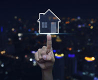 Hand pressing house icon with copy space over blurred light city. Tower background, Real estate concept Stock Photo