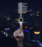 Hand pressing key with business words over blurred light city to Royalty Free Stock Images