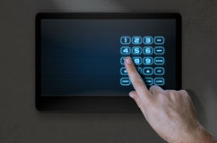 Hand Pressing Modern Home Security. A male hand pressing the screen of a home security control panel with a numeric keypad - 3D render Stock Photo