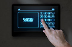 Hand Pressing Modern Home Security. A male hand pressing the screen of a home security control panel with words that read system armed - 3D render Stock Images