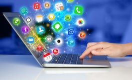 Hand pressing modern laptop with mobile app icons and symbols Stock Image